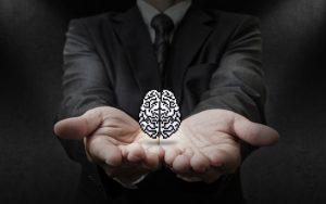 Um homem, com as mãos espalmadas, segurando um cérebro