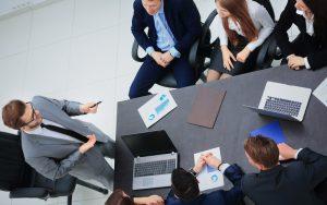 Reunião de executivos em torno de uma mesa, enquanto um deles fala, de pé.