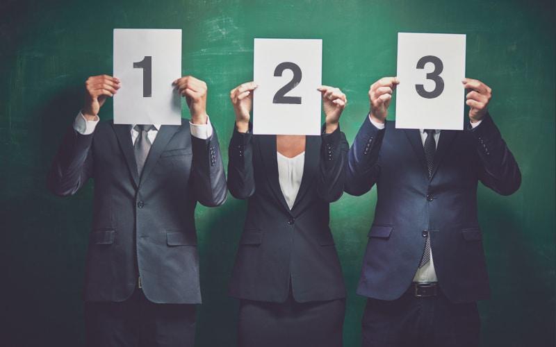 Três executivos - dois homens e uma mulher - segurando folhas com números de 1 até 3