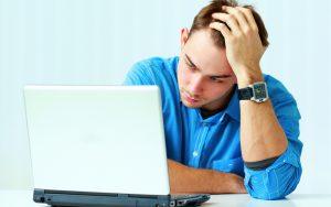 Homem sentando em frente ao computador