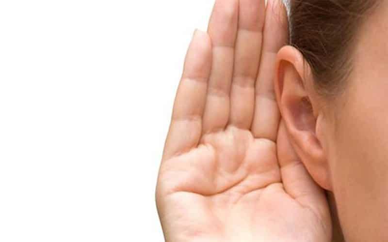 Pessoa com a mão na orelha, ouvindo.
