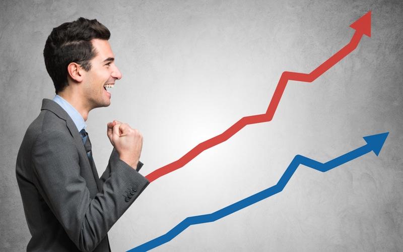 Homem em frente a um gráfico ascendente com linhas vermelha e azul