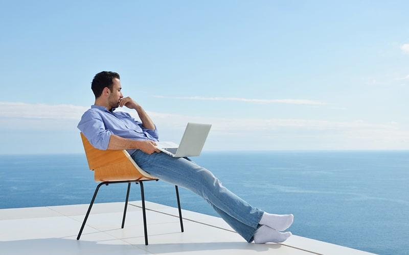 Homem sentado com notebook no colo em frente ao mar