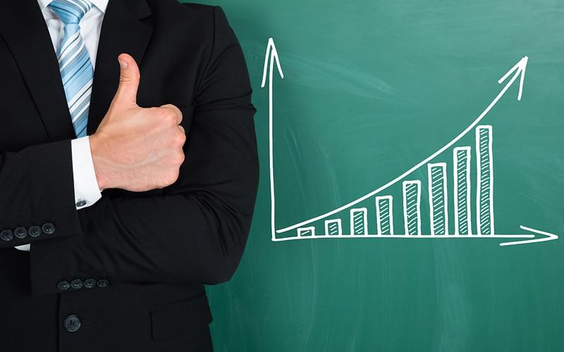 Homem fazendo sinal de positivo ao lado de um gráfico ascendente