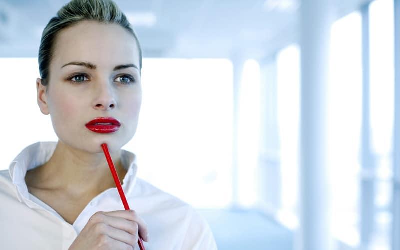 Mulher segurando um lápis e pensando